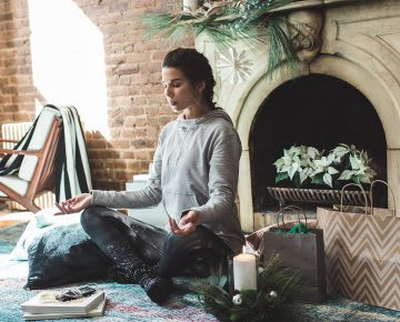 Women meditates next to her Christmas gifts finding calm in chaos