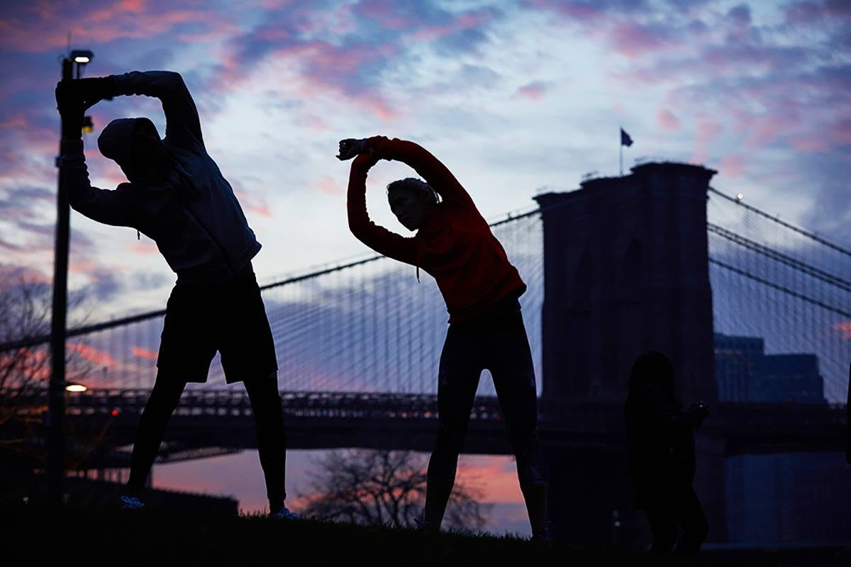 two runners stretching in front of a bridge motivating coach how to clear the hurdle