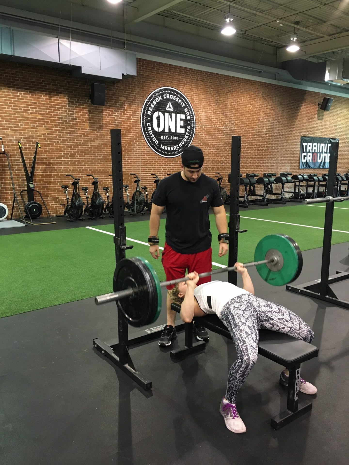 woman lifting weight with fitness trainer why women should go to the weight room