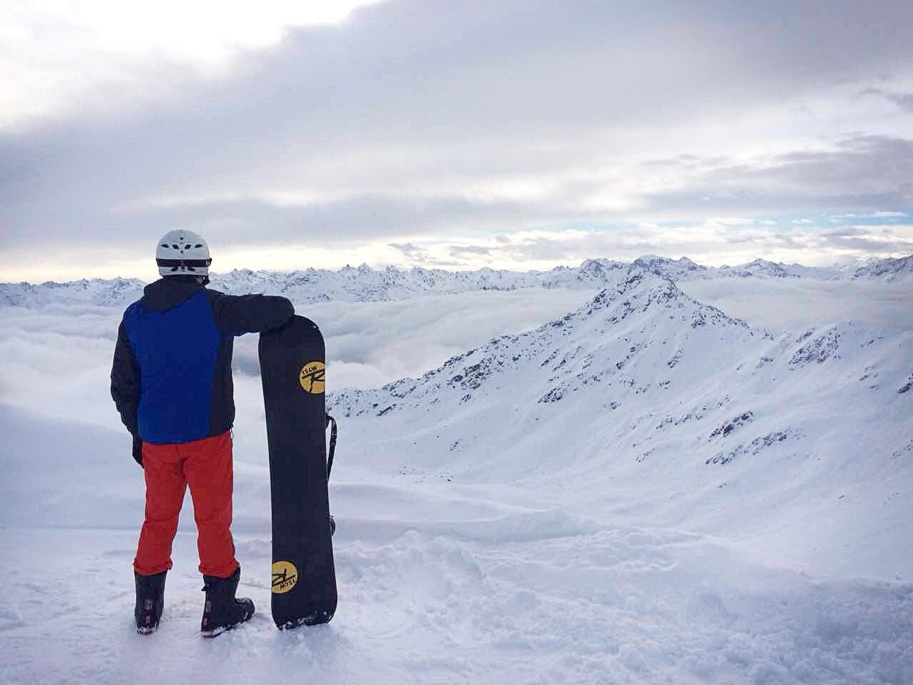 Snowboarder looking over mountains working abroad dream career