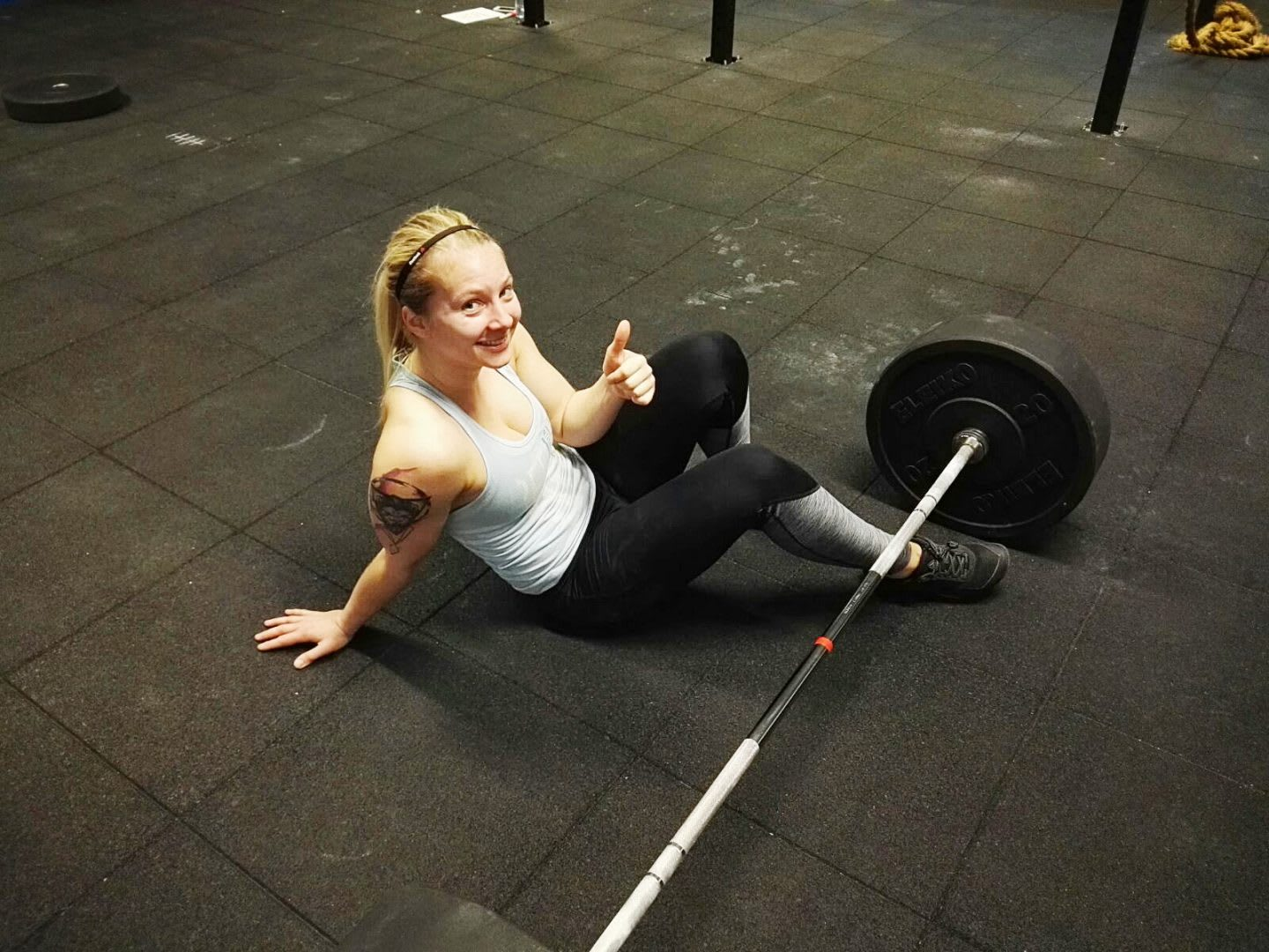 CrossFit girl sitting on the ground next to a barbell showing a thumbs up self-confidence letter to your haters training
