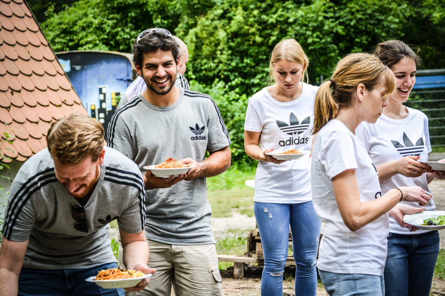 group of people in adidas shirts smile and eat lunch