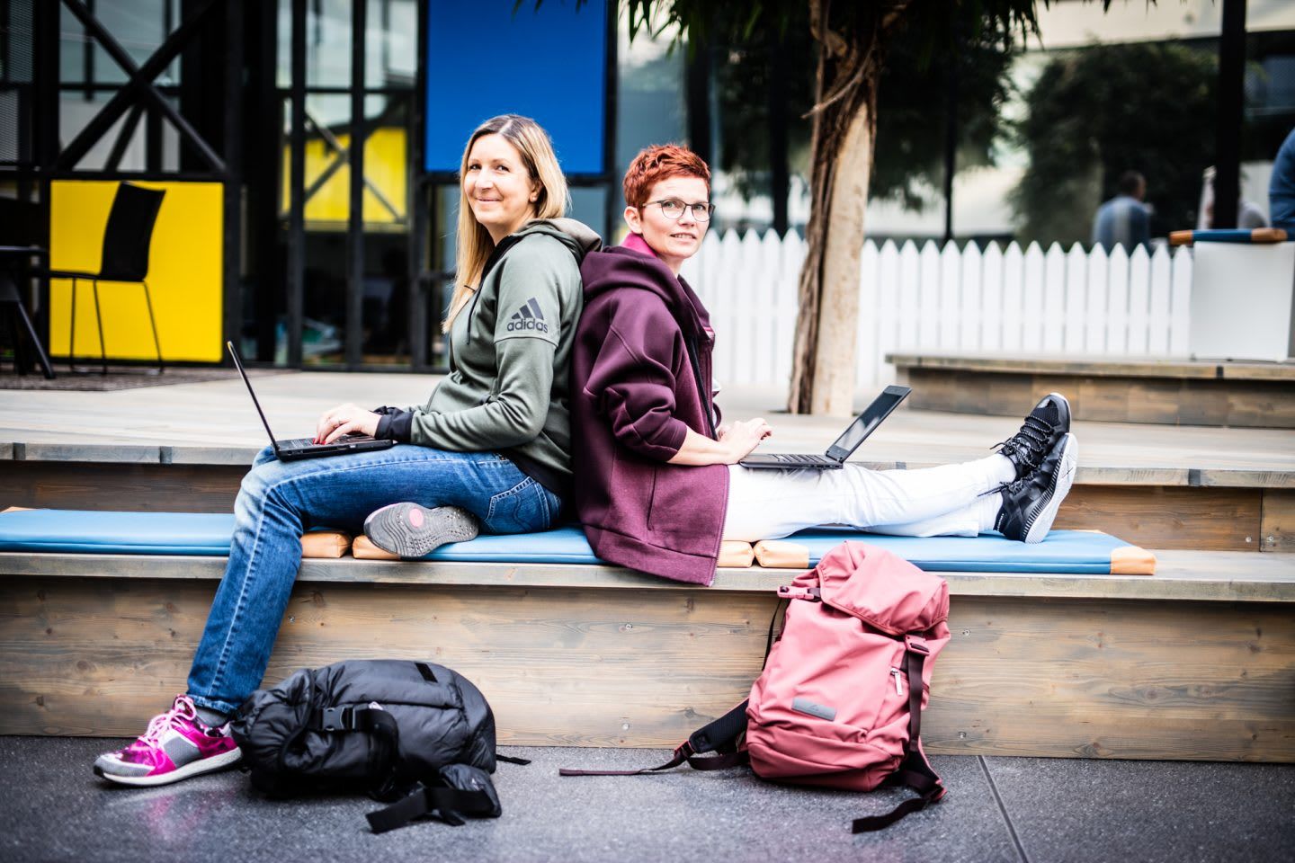 Two Women sitting back to back holding laptops job sharing interview at adidas