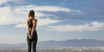 Female yoga runner standing on a hill looking down to the city. adidas women stretching trends, digital, Future Fit forecast 2017