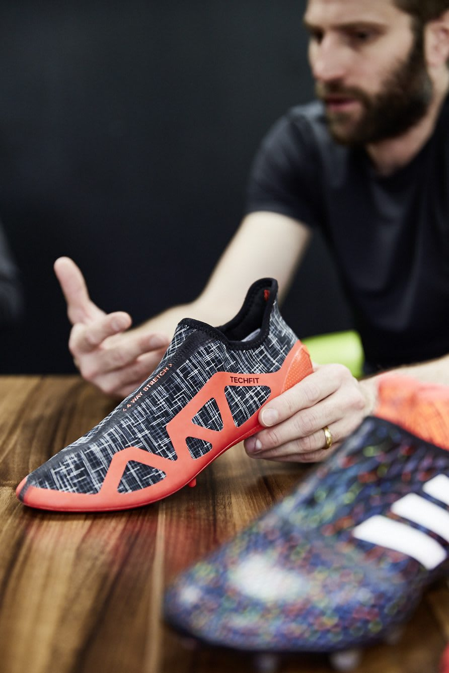 Man holding adidas GLITCH football boot and interchangeable skin on the table