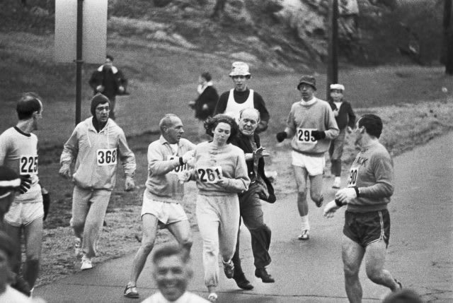 Trainer Jock Semple -- in street clothes -- enters the field of runners (left) to try to pull Kathy Switzer (261) out of the race. Male runners move in to form a protective curtain around female track hopeful until the protesting trainer is finally wedged out of the race