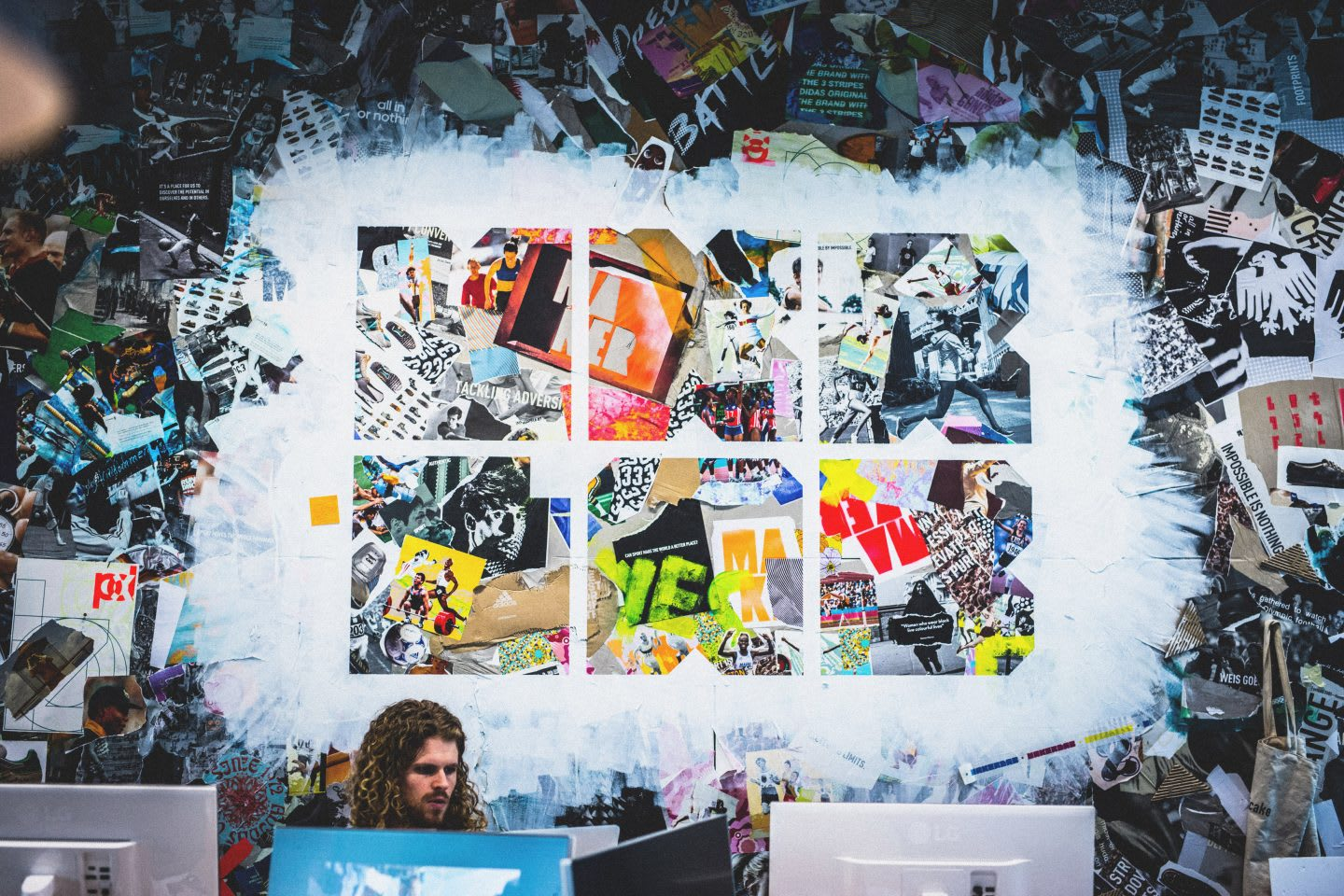 Man sitting in front of creative wall art, painting; adidas-Makerlab-creativity-employees-creators-wall-painting-artwork