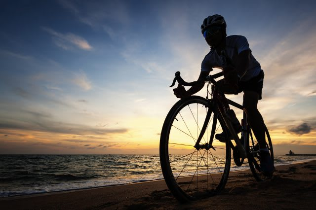 Young man cycling on the beach during sunset