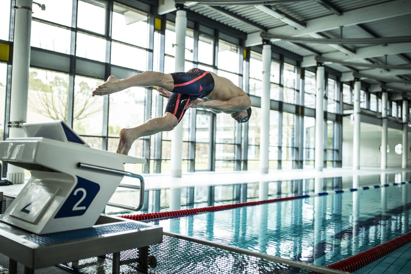 swimmer jumping from starting block marco koch training routine competition rewards hard work
