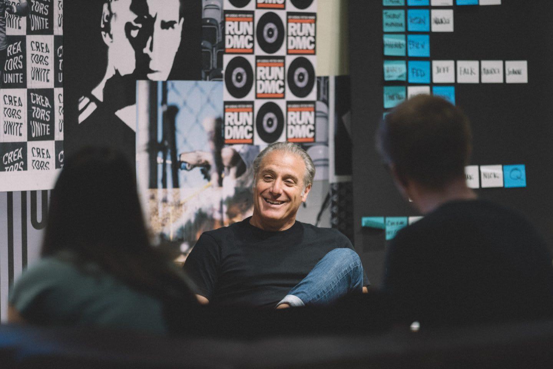 Paul Gaudio sitting on a chair at the Brooklyn creator Farm laughing