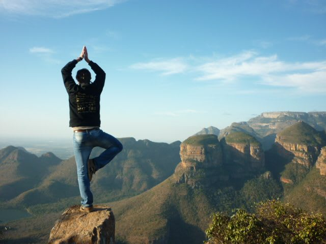 guy standing on a rock doing a the tree yoga pose while enjoying the view