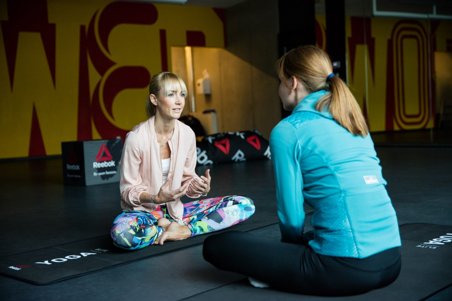 two women sitting in gym on yoga mat anna kleb yoga entrepreneur reebok