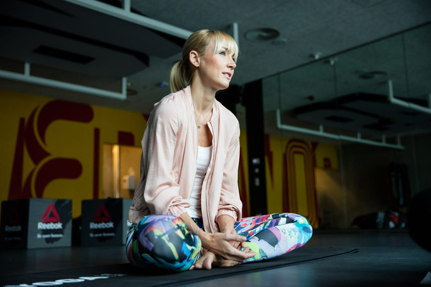blonde woman sitting on yoga mat in gym Anna Kleb Reebok Entrepreneur Strala Yoga
