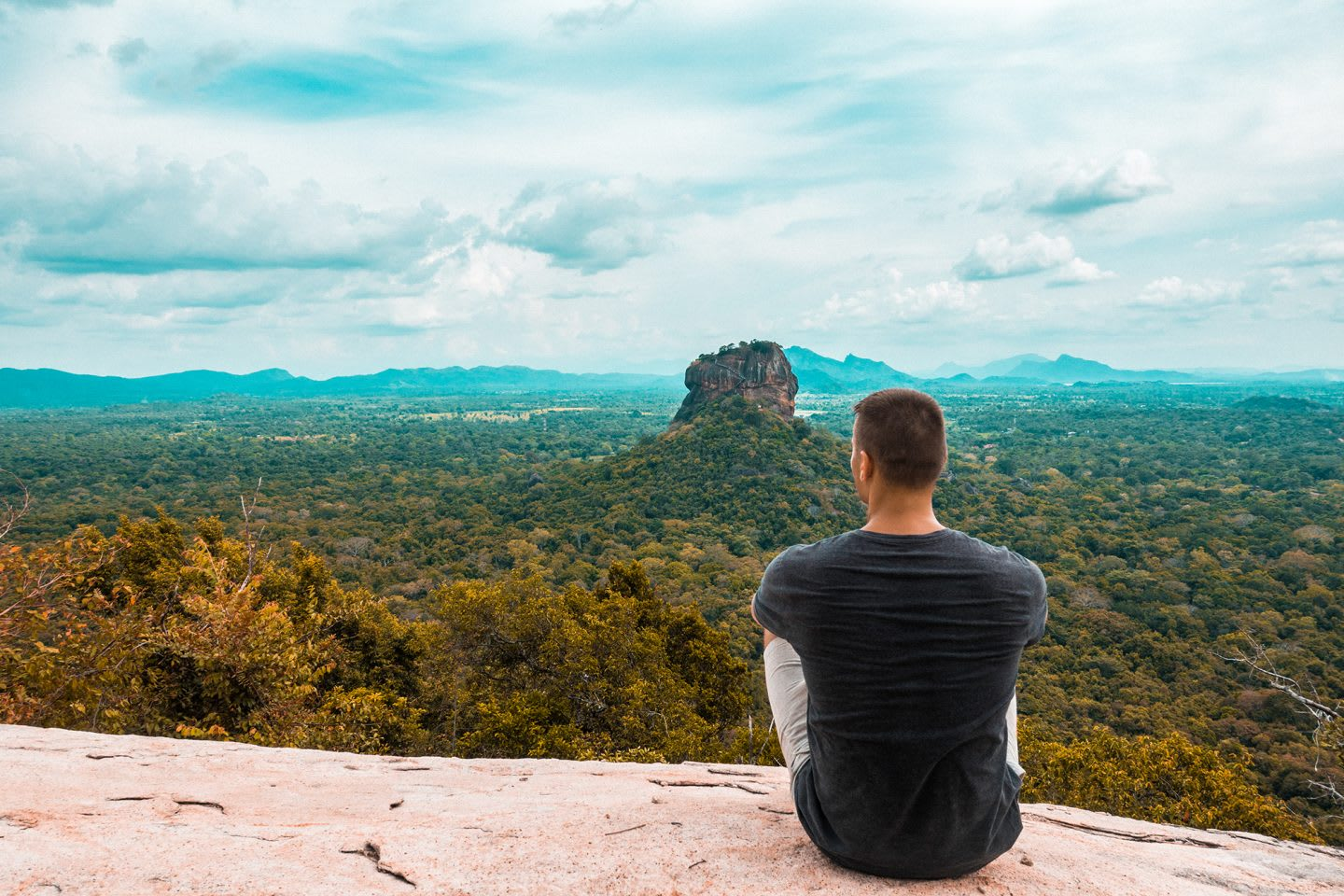 Man sitting on the edge of a canyon while enjoying the view