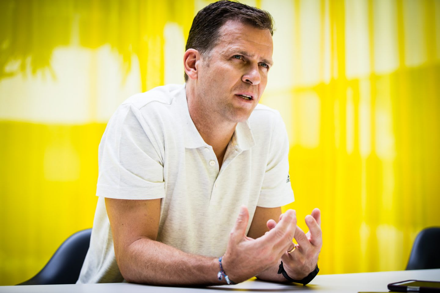 Oliver Bierhoff wearing white poloshirt giving an interview in front of a yellow background, Oliver Bierhoff_DFB_Manager_Interview_adidas_GamePlan A, German national football team