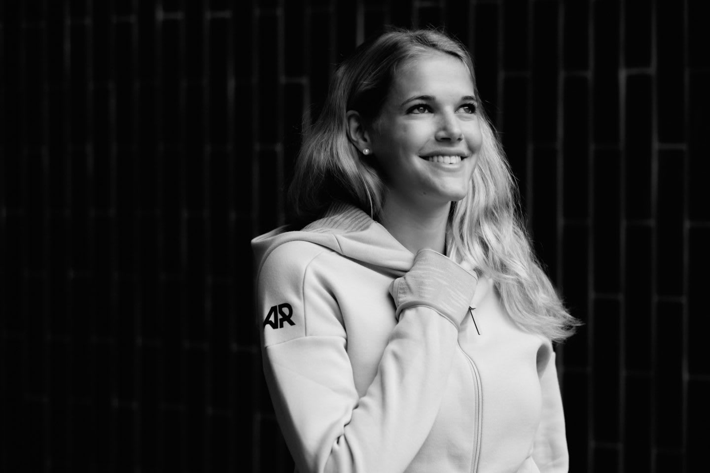Back and white picture, girl smiling in front of a black background and wearing an adidas Runners track top, Simone Luder_adidas Runners_GamePlan A