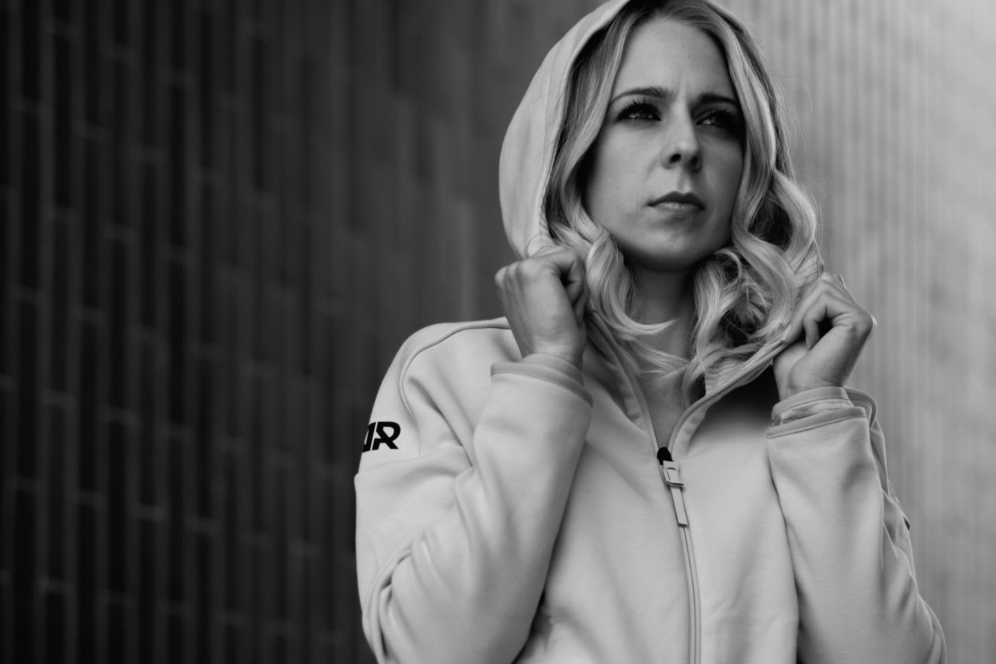 black and white picture of a woman looking concentrated and wearing an adidas Runners track top in front of a black background, Larissa Gerhard_adidas Runners_GamePlan A