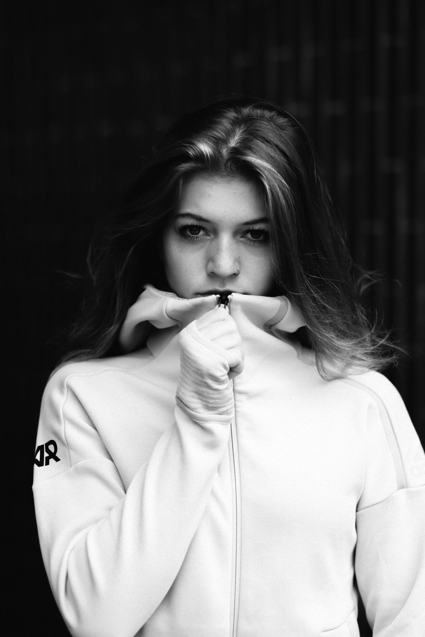 Black and white picture of a woman wearing a white adidas Runners track top and standing in front of black background, Claudia Sch+¦ttli-Serano_adidas Runners_GamePlan A