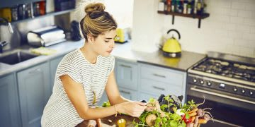 High angle view of young woman plucking mint leaves. Female is wearing casuals in kitchen. She is preparing food from recipe on tablet at kitchen island.