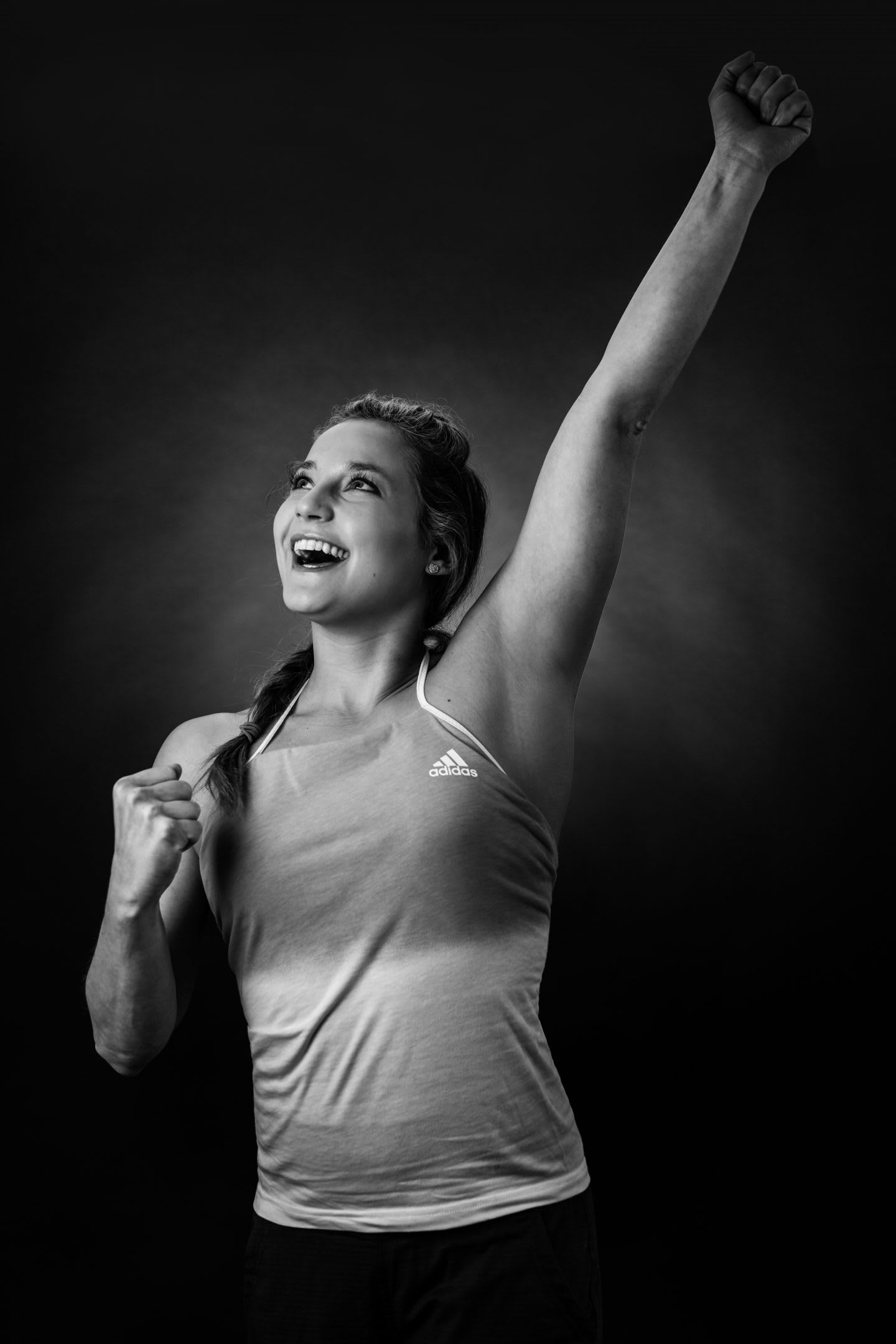 black and white photography of professional climber and adidas athlete Sasha DiGiulian doing a winning pose; Sasha-DiGiulian-climber-adidas-Terrex-Gameplan A-gesture
