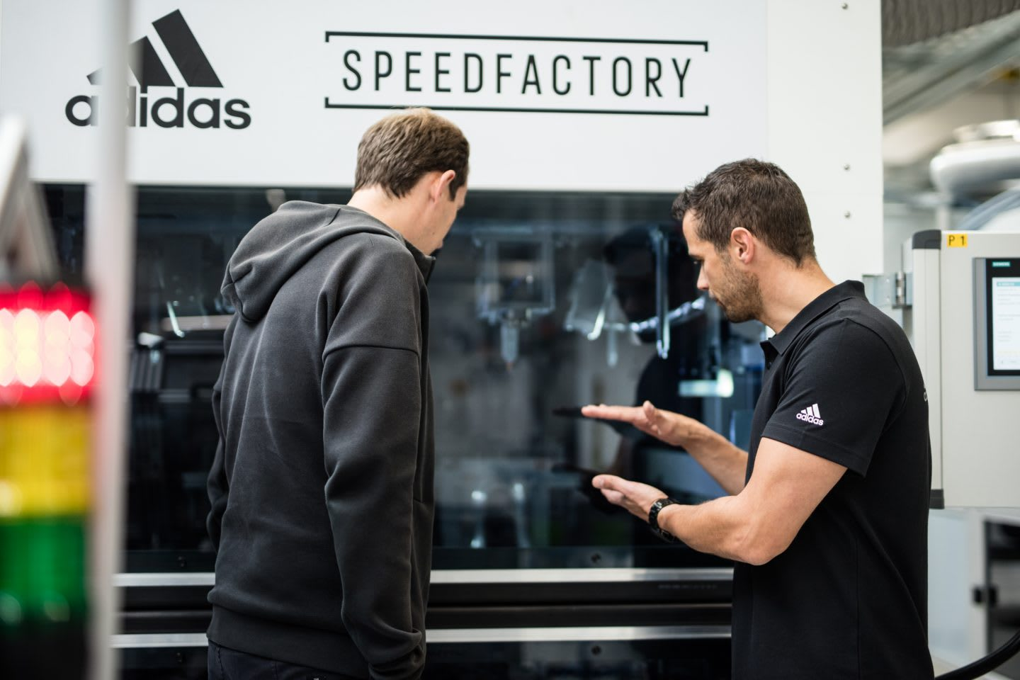 Engineers talking to each other in front of a machine of the adidas SPEEDFACTORY, adidas-SPEEDFACTORY-OECHSLER-interview-robotics-GamePlanA