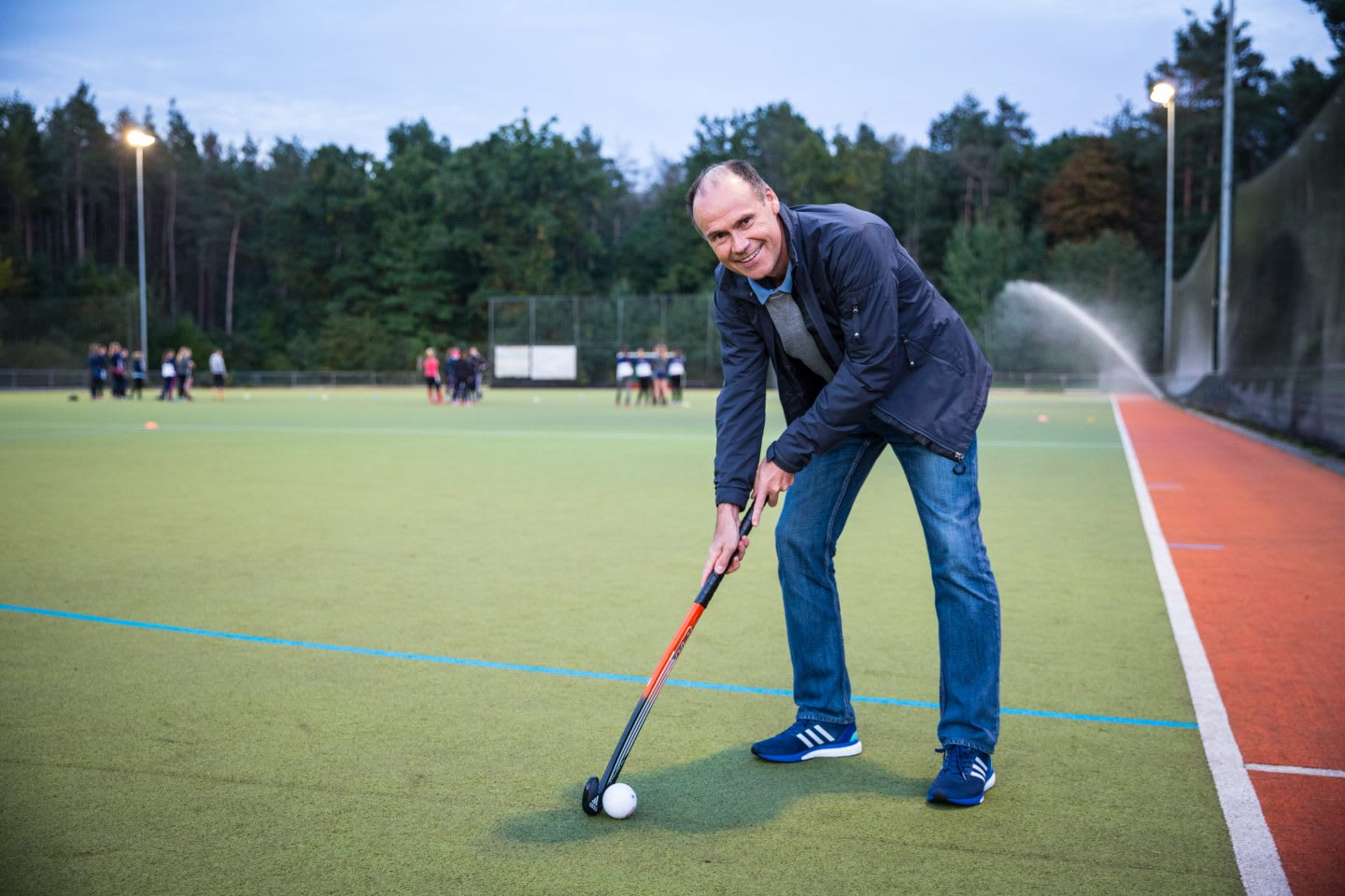 Coach is smiling at the camera while demonstrating a proper field hockey stance with the stick and ball.