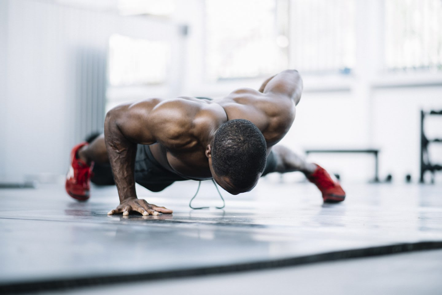 A shirtless man in a gym is doing a one armed push-up.