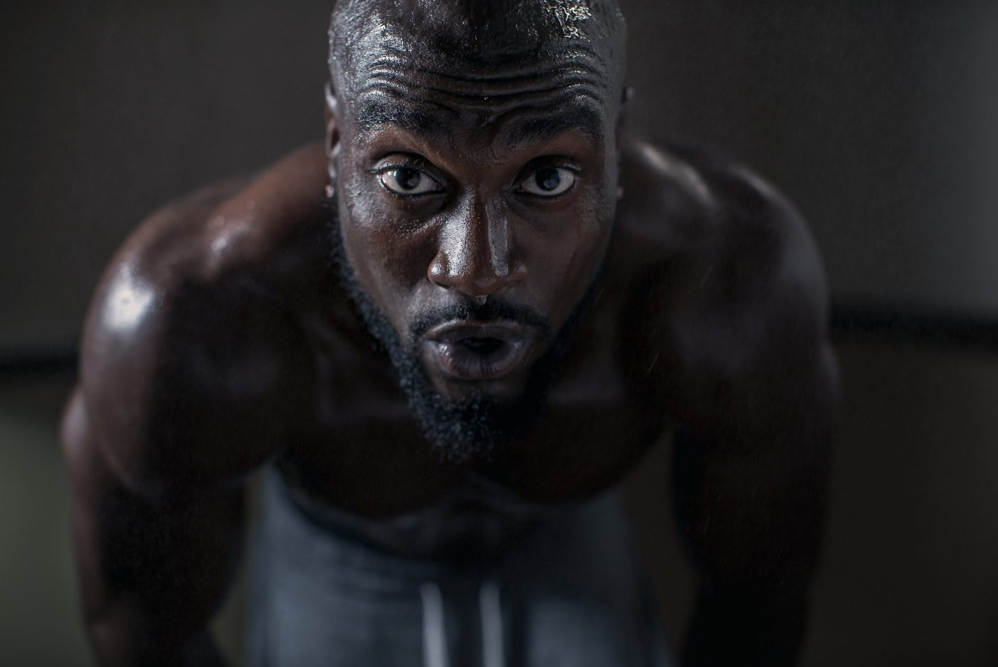 A man is looking deeply into the camera while exhaling during a strength workout.