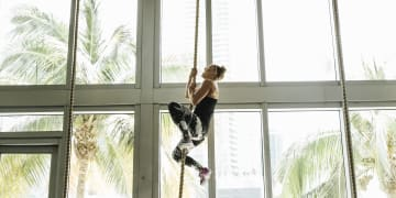 Woman is climbing up a rope_Crossfit