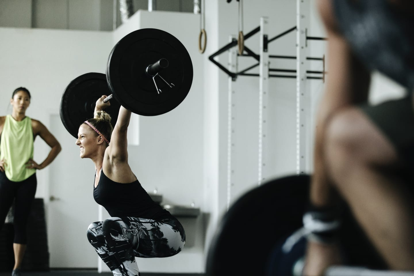 Woman lifting weight with another woman watching in the background.