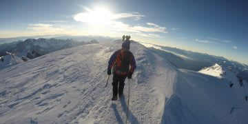 A mountaineer walking on a snowy crest with the sun in the background. GamePlan A, adidas, mountaineering, risk taking