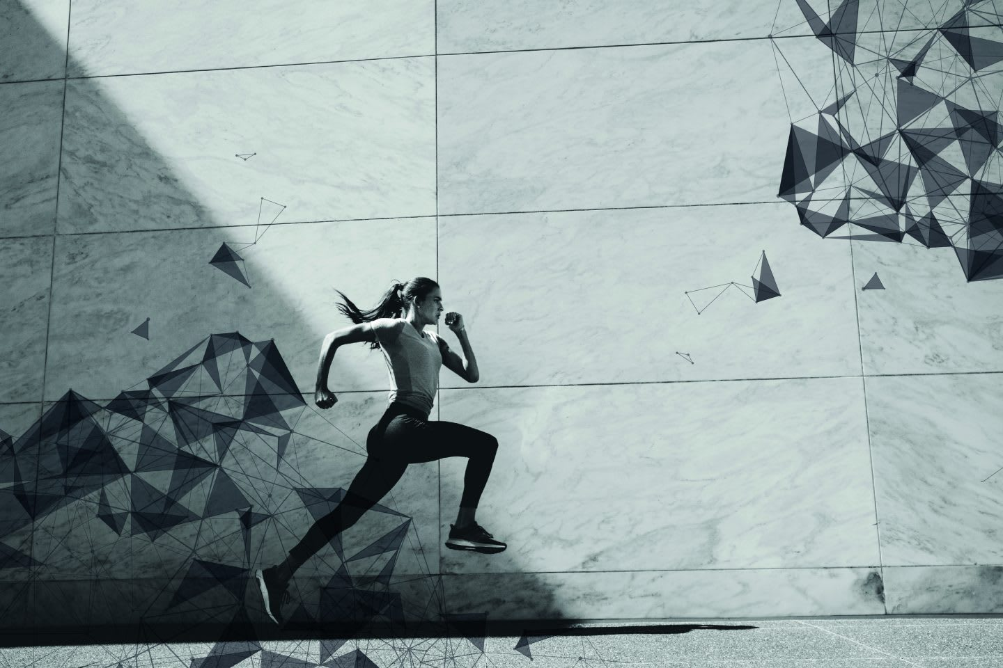 Woman running against a cement backdrop.