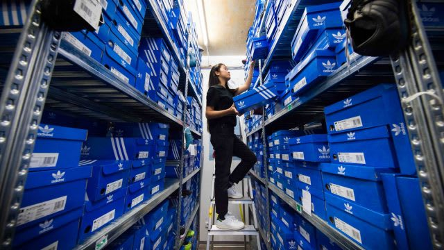 women is organizing adidas shoe boxes in a storage from a direct perspective