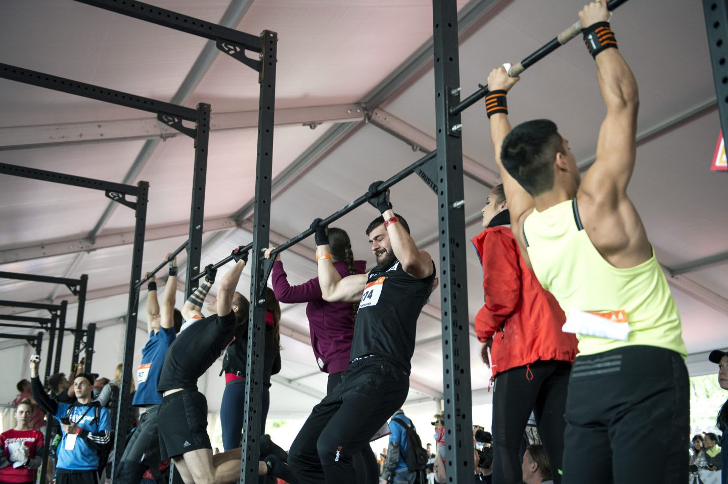A group of men are doing pull ups at a bar while they are being monitored by referees. Crossfit; Motivation; Competition; Hard work; Workout
