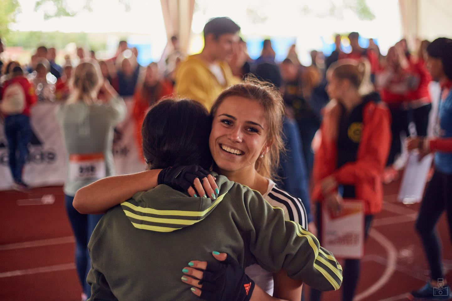 A smiling woman in sports gear is hugging another woman on a track field. Motivation; Passion; Competition; Adidas; Reebok; GamePlan A