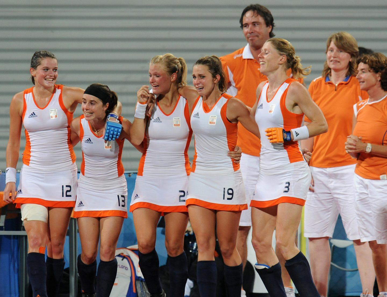 five teammates of the Dutch women's hockey team gathering after winning a match