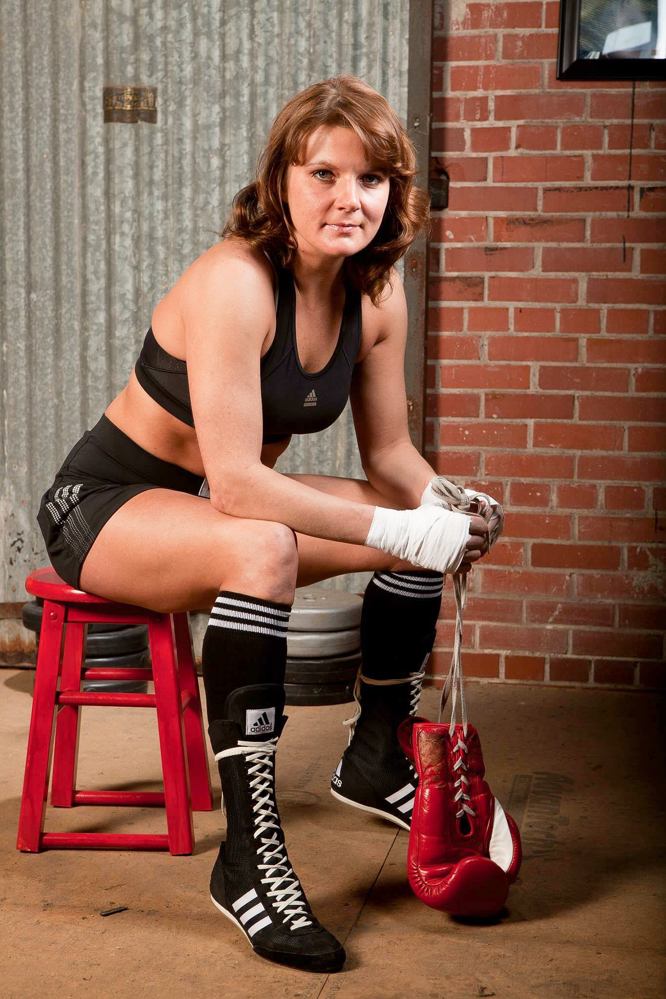 Lisa Garland is sitting on a stool in boxing gear, holding her boxing gloves in her hands. Boxing; adidas; training; workout; fight, goals; GamePlanA