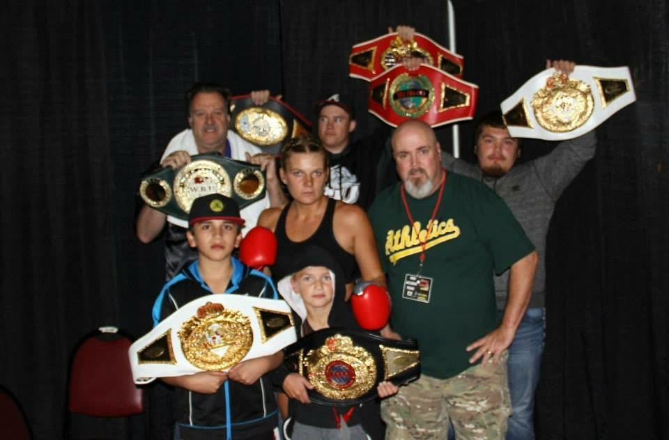 Lisa Garland is in fighting stance, surrounded by friends and family holding up her championship belts. Motivation; win; fight; boxing; GamePlanA; adidas; Goals; Dream; Role Model