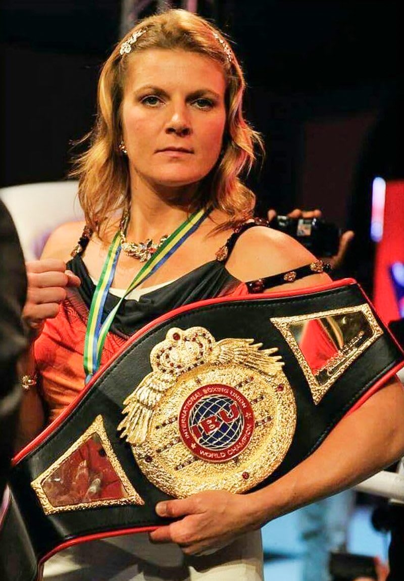 Lisa Garland is facing the camera, holding one of the belts she won in boxing. Motivation; GamePlanA; Goals; Champion; Feminine; Hard work; Boxing
