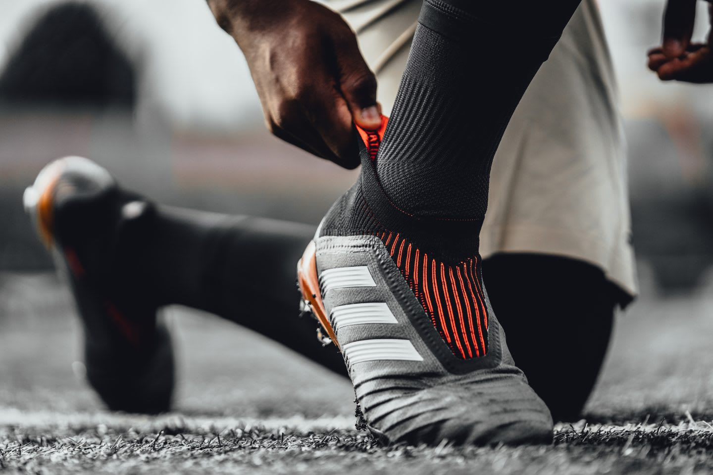 A person is kneeling on the ground, putting on the new black and white Predator boot with red details. Icon,; Legend; adidas; football; boot; soccer; Innovation; GamePlan A