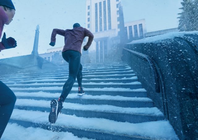 two runners jogging up some stairs to reach a high building in winter to motivate themselves to reach their goals