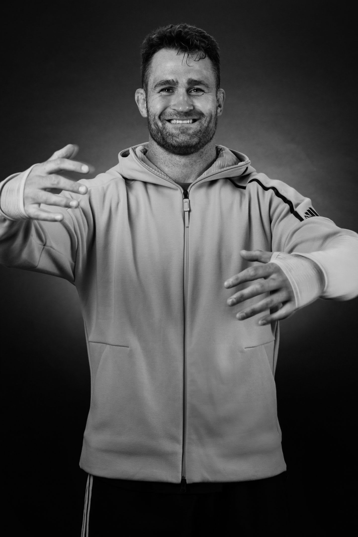 Black and white of rugby player James Horwill holding his arms in the position of a hug.