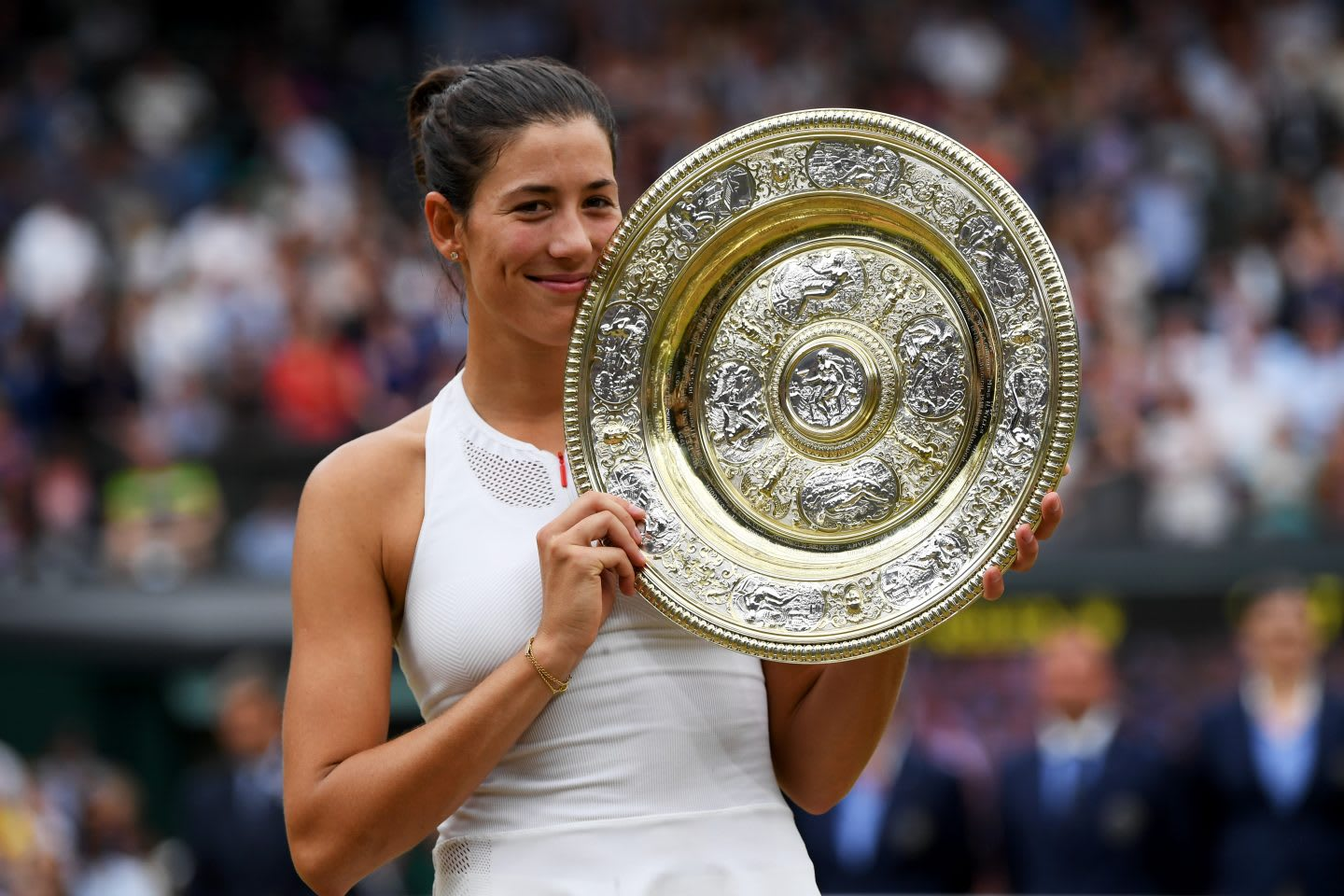 Garbine Muguruza is standing on the tennis court, holding a trophy. Athlete; Tennis; Champion; Wimbledon; adidas; GamePlan A; Motivation; Win; Dedication; Inspiration