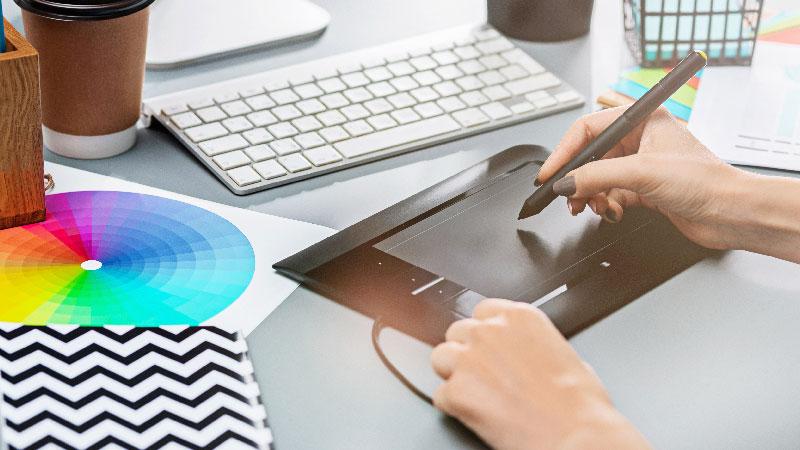 Ilustradora trabalhando com uma mesa digitalizadora para ganhar dinheiro no Instagram