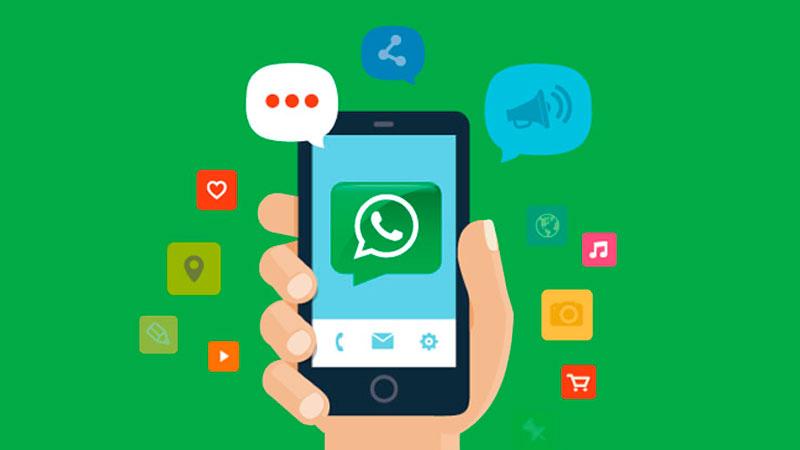 Mão segurando smartphone com WhatsApp aberto e ícones de comunicação em sua volta