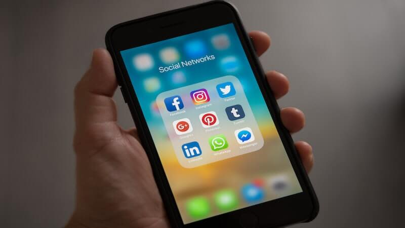 The image shows a person holding a smartphone where in the screen there are several social media icons