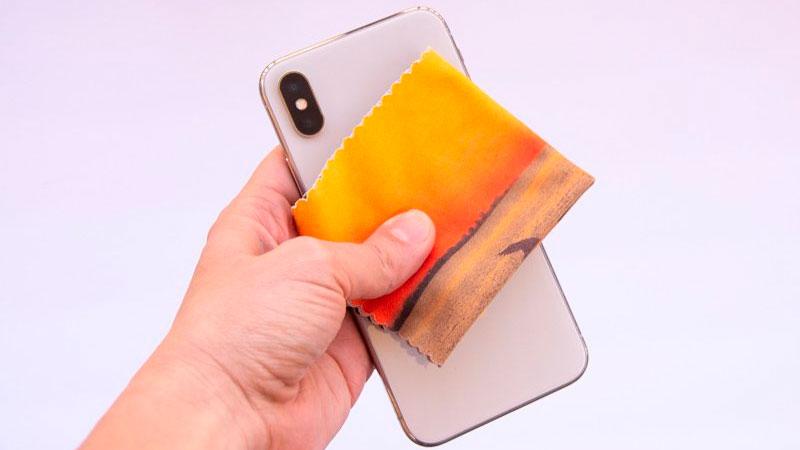 Mão segurando um celular e uma flanela para limpeza