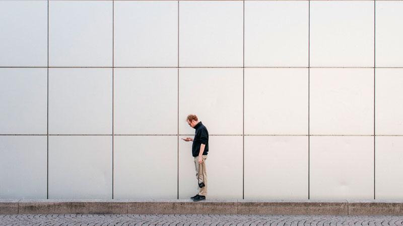 Homem centralizado em um um fundo quadriculado de uma parede
