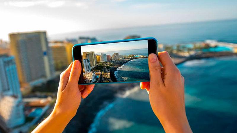 pessoa usando seu smartphone para tirar uma foto de uma praia