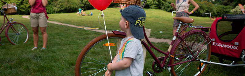 criança segurando um balão ao lado de uma bicicleta em um parque